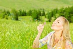 Burbujas que soplan de la muchacha linda al aire libre Fotografía de archivo