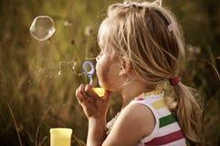 Burbujas que soplan de la muchacha linda en un campo imágenes de archivo libres de regalías