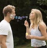 Burbujas que soplan de la muchacha rubia Imagen de archivo