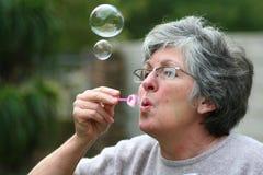 Burbujas que soplan de la mujer fotografía de archivo libre de regalías