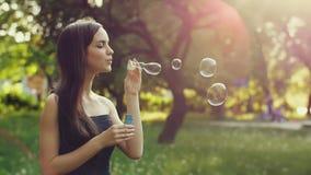 Burbujas que soplan de la mujer adolescente almacen de video