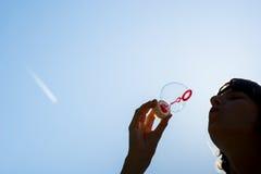 Burbujas que soplan de la mujer contra un cielo azul Fotos de archivo