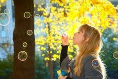 Burbujas que soplan de la mujer en parque Imagenes de archivo