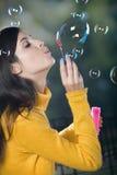 Burbujas que soplan de la mujer joven Imagenes de archivo