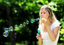 Burbujas que soplan de la mujer joven Fotografía de archivo