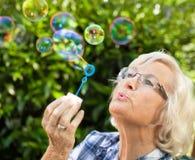 Burbujas que soplan de la mujer mayor Fotografía de archivo