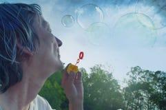 Burbujas que soplan de la mujer mayor Imagen de archivo libre de regalías