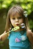 Burbujas que soplan de la niña afuera Imágenes de archivo libres de regalías