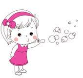 Burbujas que soplan de la niña linda Imagenes de archivo