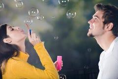 Burbujas que soplan de los pares, al aire libre Foto de archivo