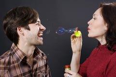 Burbujas que soplan de los pares felices Imagen de archivo