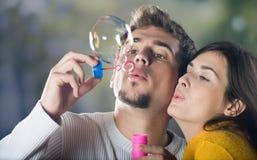 Burbujas que soplan de los pares jovenes Imagenes de archivo
