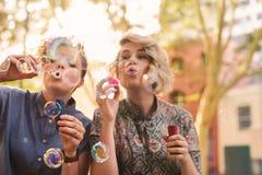 Burbujas que soplan de los pares lesbianos jovenes despreocupados afuera en la ciudad Foto de archivo