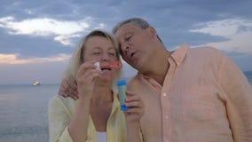 Burbujas que soplan de los pares mayores en la playa almacen de video