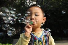 Burbujas que soplan de un muchacho Fotografía de archivo
