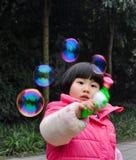 Burbujas que soplan de una muchacha de la litera Imágenes de archivo libres de regalías