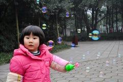 Burbujas que soplan de una muchacha de la litera Imagen de archivo libre de regalías