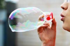Burbujas que soplan de una mujer hermosa fotos de archivo