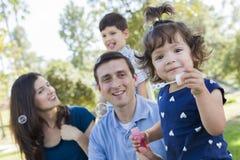 Burbujas que soplan del bebé joven lindo con la familia en parque Fotos de archivo