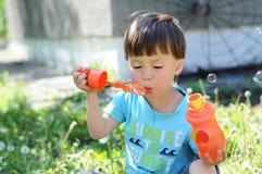 Burbujas que soplan del muchacho afuera Fotos de archivo libres de regalías