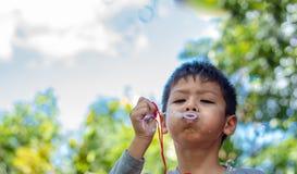 Burbujas que soplan del muchacho de Asia del retrato en jardín fotos de archivo