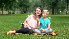 Burbujas que soplan del muchacho feliz, madre que juega con el hijo en el parque, vacaciones comunes felices imagen de archivo
