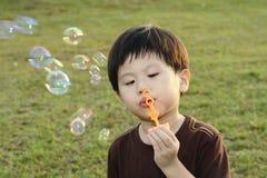 Burbujas que soplan del muchacho joven Fotos de archivo