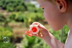 Burbujas que soplan del muchacho joven Imagen de archivo libre de regalías