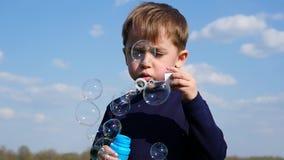 Burbujas que soplan del ni?o peque?o Burbujas de jab?n del ni?o que soplan feliz en primavera en el parque C?mara lenta metrajes