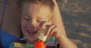Burbujas que soplan del pequeño niño feliz al aire libre metrajes