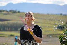 Burbujas que soplan despreocupadas de la mujer joven en país Imagen de archivo libre de regalías