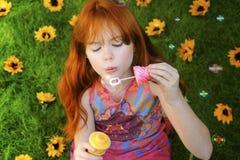 Burbujas que soplan dirigidas rojas de la muchacha Fotos de archivo libres de regalías