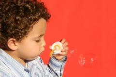 Burbujas que soplan - fondo rojo Foto de archivo libre de regalías