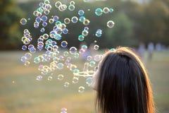 Burbujas que soplan hermosas de la mujer joven afuera Fotografía de archivo libre de regalías