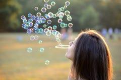Burbujas que soplan hermosas de la mujer joven afuera Fotos de archivo libres de regalías