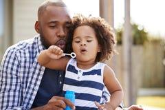 Burbujas que soplan negras jovenes del padre y de la hija afuera imagenes de archivo