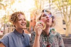 Burbujas que soplan sonrientes de los pares lesbianos jovenes junto en la ciudad Imagen de archivo