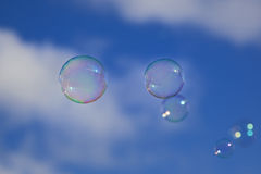 Burbujas sobre un cielo azul con las nubes Fotos de archivo
