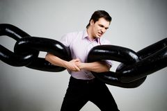 Burden. Portrait of tense businessman with two sections of huge chain over grey background Royalty Free Stock Images