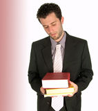 Burdened with work. Young brown-haired, white man, wearing formal attire, holding books and looking resigned or exhausted at them Royalty Free Stock Photography