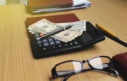Bureau avec des dollars US, smartphone avec l'écran noir, stylo, Photo stock