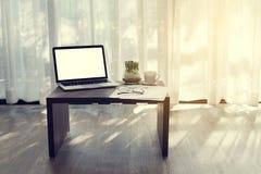 Bureau avec l'écran vide sur l'ordinateur portable, tasse de café, moderne Photographie stock libre de droits