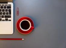 Bureau avec l'ordinateur portable, les verres d'oeil, le stylo, le bloc-notes et une tasse de café Photographie stock libre de droits