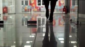 Bureau avec la porte en verre et aller jambes femelles dans des chaussures noires banque de vidéos
