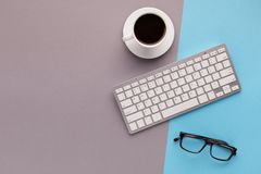 Bureau avec la tasse et le clavier de café sur le fond coloré Photos libres de droits