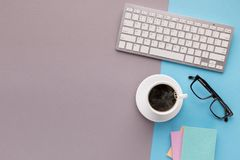 Bureau avec la tasse et le clavier de café sur le fond de couleur deux Photo libre de droits