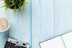Bureau avec le bloc-notes, l'appareil-photo, le café et la fleur Photo stock