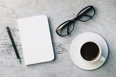 Bureau avec le bloc-notes, la tasse et les verres Photographie stock libre de droits