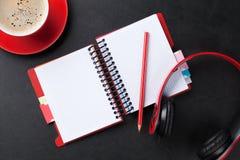 Bureau avec le bloc-notes, le café et les écouteurs Images libres de droits
