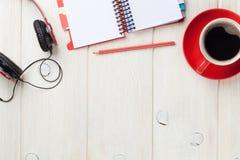 Bureau avec le bloc-notes, le café et les écouteurs Photos stock